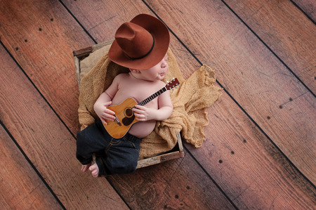 baby playing: A three week old baby boy wearing a cowboy hat and jeans and playing a tiny acoustic guitar. His lips are pursed, as if whistling. He is lying in a wooden crate lined with burlap. Shot in the studio on a rustic, wood background.