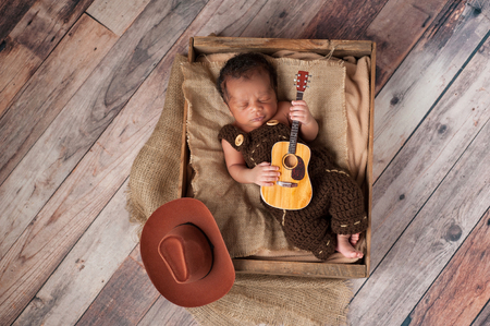 A two week old baby boy wearing crocheted overalls and playing a tiny acoustic guitar. He is lying in a wooden crate lined with burlap. Shot in the studio on a rustic, wood background.
