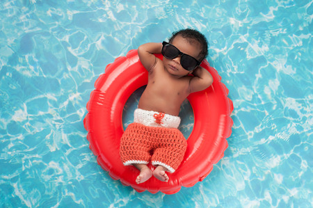 float tube: Two week old newborn baby boy sleeping on a tiny inflatable swim ring. He is wearing crocheted board shorts and black sunglasses.