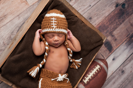A two week old newborn baby boy sleeping in wooden crate and wearing a crocheted American football costume. Stock Photo