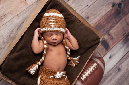Un niño de dos semanas de edad bebé recién nacido que duerme en caja de madera y que lleva un traje de fútbol americano de ganchillo.