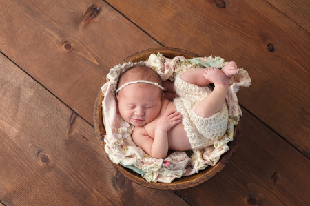 cream colored: A ten day old newborn baby girl sleeping in a little, wooden bowl. She is wearing cream colored shorts and a matching headband. Shot in the studio on a wood background.