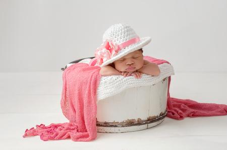 Un retrato de una muchacha durmiente tres semanas de edad, recién nacido, bebé que llevaba un elegante, sombrero de ala ancha de Pascua con flores de color rosa. Ella está durmiendo en un blanco, cubo de la vendimia, de madera.