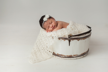A three week old newborn baby girl sleeping in a little, wooden bucket. She is wearing a cream colored bow headband. Shot in the studio on a white background.