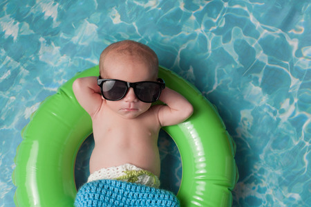 Four week old newborn baby boy sleeping on a tiny inflatable swim ring. He is wearing crocheted board shorts and black sunglasses.