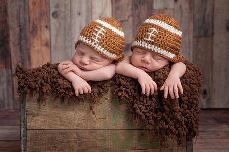 Cuatro semanas de edad fraternales, gemelos, los bebés recién nacidos que duermen en una época, el cajón de madera y el uso de tapones en forma de fútbol. Un disparo en el estudio sobre un fondo de madera.