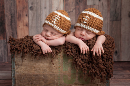 Four week old fraternal, twin, newborn baby boys sleeping in a vintage, wooden crate and wearing football shaped caps. Shot in the studio on a wood background.