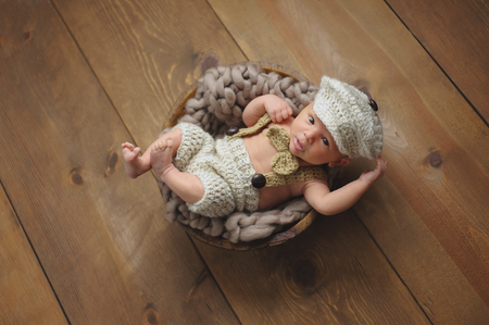 newsboy cap: Overhead shot of an alert, 3 week old, newborn baby boy wearing a crocheted little man suit with newsboy cap and bowtie. He is lying inside of a tiny, wooden bowl and looking at the camera. Stock Photo