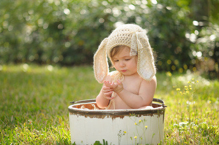 A ten month old baby girl wearing a tan, crocheted, bunny bonnet. She is sitting in a white, wooden bucket and looking down at her hands. Shot outdoors with green grass and backlighting.