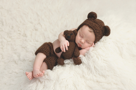 crocheted: Three week old newborn baby boy wearing a brown, crocheted bear hat and shorts. He is sleeping on a white flokati rug and holding a matching stuffed bear toy.