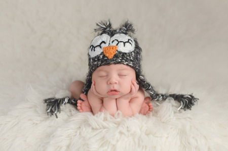 curled up: Three week old newborn baby boy wearing a crocheted owl hat. Hes in a cute, curled up, chin on hands pose and sleeping on a white flokati rug. Stock Photo