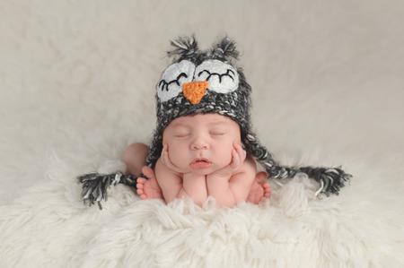 Tres semanas de edad bebé recién nacido que lleva un sombrero de ganchillo búho. Está en un lindo, acurrucado, barbilla en las manos pose y durmiendo en una manta flokati blanco.