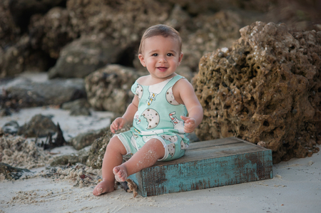 one year old: A one year old baby boy, smiling and sitting on a wooden crate. Shot outdoors on a beach with rocks in the background. Stock Photo