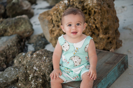 one year old: A one year old baby boy sitting on a blue wooden crate. Shot outdoors on a beach with rocks in the background. Stock Photo