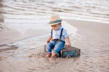 one year old: A one year old baby boy sitting on a blue, wooden crate. Shot outdoors on a sandy beach. Stock Photo