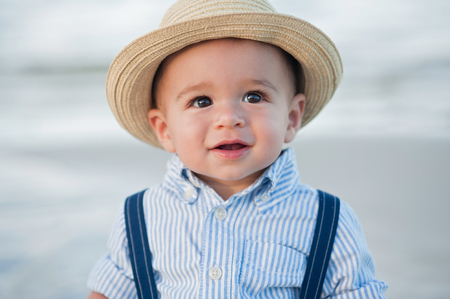 one year old: A headshot of a one year old baby boy wearing a straw fedora hat.