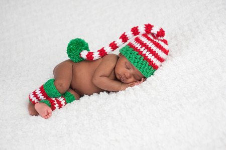 newborns: A one month old baby girl wearing a crocheted, red, white and green stocking cap and matching leg warmers. Photographed on a white, fluffy blanket.