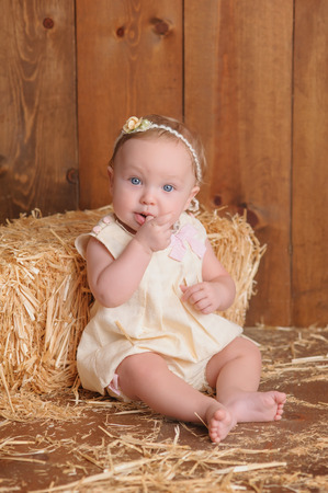yellow dress: A six month old baby girl wearing a yellow dress. She is sitting and leaning against a small straw bale. Shot in the studio on a wood paneled floor and background.