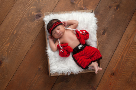 faux: Eleven day old newborn baby boy wearing boxing shorts. He is lying in a wooden crate lined with white, faux fur and has boxing gloves draped around his neck. Shot in the studio on a wood background. Stock Photo