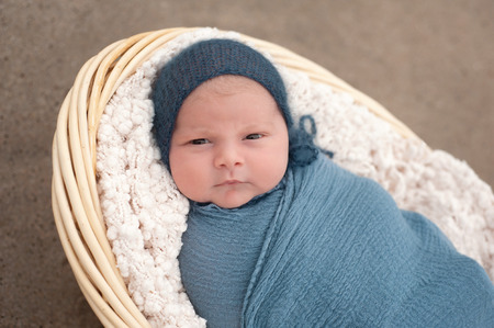 beach wrap: An alert, three week old, newborn, baby boy swaddled in a blue wrap and wearing a blue bonnet. He is lying in a wicker basket and looking at the camera. Shot outdoors on a sandy beach.