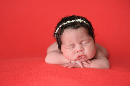 coral colored: Portrait of two week old, sleeping, newborn baby girl. She is wearing a rhinestone headband and lying on a coral colored blanket.