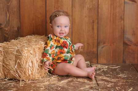 six month old: A smiling, six month old, baby girl wearing a floral romper in fall colors. She is sitting and leaning against a small straw bale. Shot in the studio on a wood paneled floor and background.