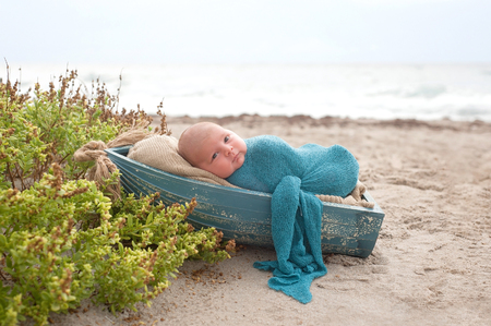 beach wrap: Three week old, newborn baby boy swaddled in a blue wrap and sleeping in a tiny, wooden boat. Photographed at the ocean with sand and beach vegetation.
