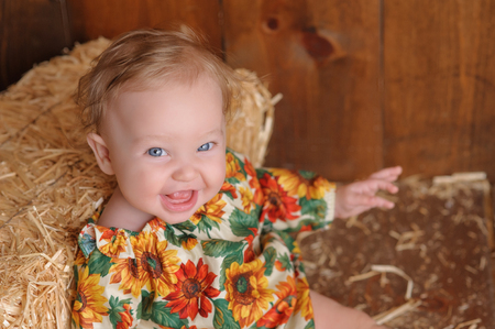 romper: A laughing, six month old, baby girl wearing a floral romper in fall colors. She is sitting and leaning against a small straw bale. Shot in the studio on a wood paneled floor and background. Stock Photo