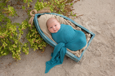 swaddled: An alert, three week old, newborn, baby boy swaddled in a blue wrap and lying in a little boat. Shot on a sand and beach vegetation background.