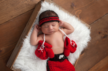 he old: Eleven day old newborn baby boy wearing boxing shorts. He is lying in a wooden crate lined with white, faux fur and has boxing gloves draped around his neck. Shot in the studio on a wood background. Stock Photo