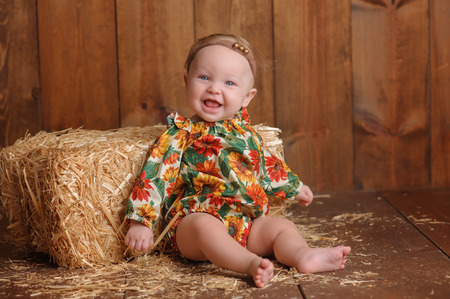 romper: A smiling, six month old, baby girl wearing a floral romper in fall colors. She is sitting and leaning against a small straw bale. Shot in the studio on a wood paneled floor and background.