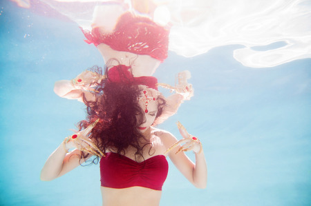 costume jewelry: An artistic, underwater portrait of a female model wearing a red bandeau top, gold Thai fingernails and a jewel headpiece.