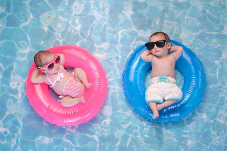 Two month old twin baby sister and brother sleeping on tiny, inflatable, pink and blue swim rings. They are wearing crocheted swimsuits and sunglasses. Reklamní fotografie - 67339924