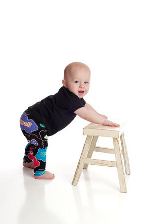 A seven month old, baby boy leaning on a bench for support as he learns how to stand. Shot on a white, seamless background.