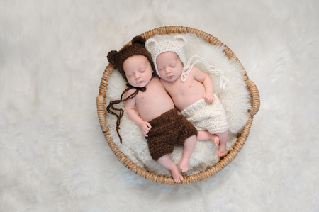 fraternal: Two month old, boy and girl fraternal twin babies. They are sleeping together in a basket wearing coordinated, crocheted, bear bonnets and shorts.