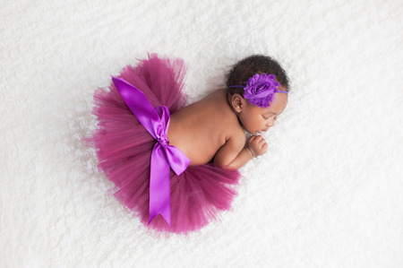 Portrait of a one month old, sleeping, newborn, baby girl. She is wearing a purple tutu and sleeping on a white blanket. Archivio Fotografico
