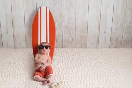 Nine day old newborn baby boy leaning againt and sleeping on a tiny, orange and white surfboard. He is wearing orange, crocheted board shorts.