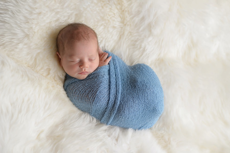 Sleeping, nine day old newborn baby boy swaddled in a light blue wrap. Shot in the studio on a white sheepskin rug.