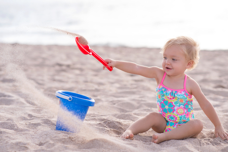 A one year old baby girl playing with a shovel and bucket in the sand. Shot outdoors on a sandy beach. Stock Photo