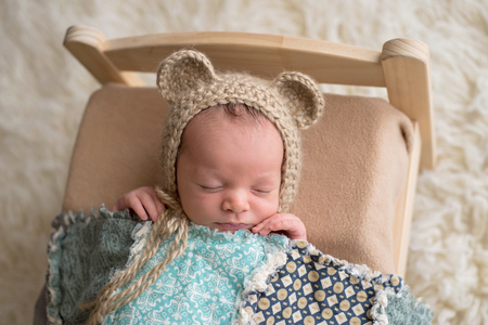Two week old newborn baby boy wearing a tan, crocheted, bear bonnet. He is sleeping on a tiny, wooden bed and covered with a blue quilt.