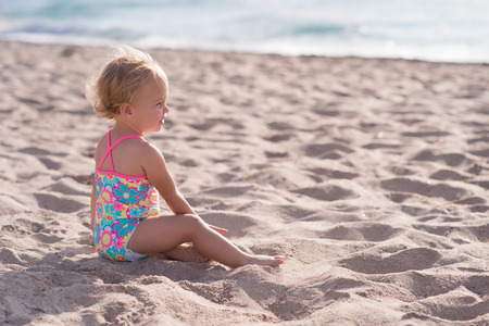 Side profile of a one year old baby girl sitting on a sandy beach. Stock Photo