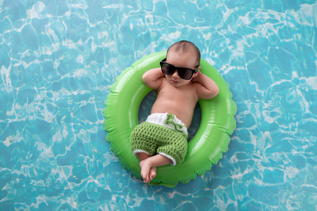 Two week old newborn baby boy sleeping on a tiny, green, inflatable swim ring. He is wearing green, crocheted board shorts and black sunglasses. 免版税图像
