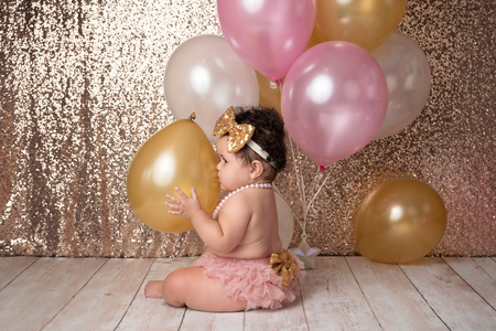 A one year old, baby girl wearing pink bloomers, a sequin headband and a string of pearls. She is holding a gold balloon and you can see her face reflected into the balloon.