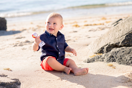 A one year old baby boy sitting on a beach and playing with a shaker toy. Stock Photo