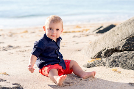 A one year old baby boy sitting on a beach and looking directly at the camera. Stock Photo