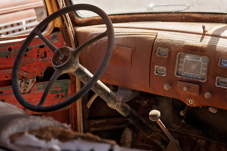 The interior of an old, rusty, antique vehicle.