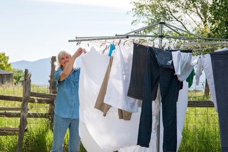 A senior woman hanging laundry on a clothesline outside to dry. Stock fotó