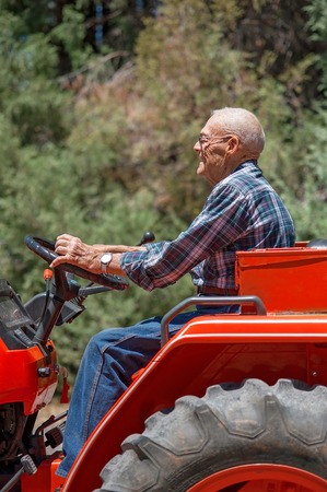 A candid portrait of a senior man operating a tractor. Stock Photo