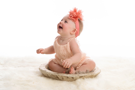 A smiling, seven month old baby girl wearing a peach colored, knitted romper.