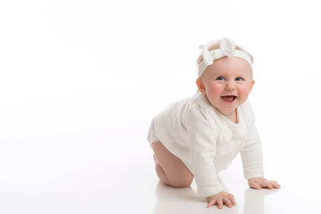 A laughing, crawling, seven month old, baby girl wearing a white shirt, diaper and headband. Shot in the studio on a white, seamless backdrop.